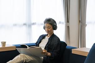 ヘッドホンをして読書をする日本人シニア女性の写真素材 [FYI04873169]