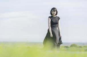 風に吹かれる若い女性の写真素材 [FYI04873358]