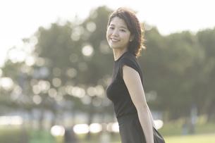 風に吹かれる若い女性の写真素材 [FYI04873364]