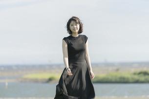 風に吹かれる若い女性の写真素材 [FYI04873367]
