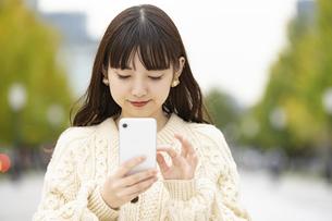 スマートフォンを使う若い女性の写真素材 [FYI04873383]