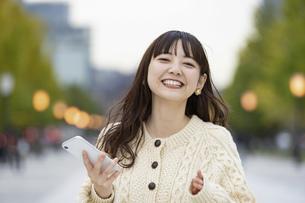 スマートフォンを使う若い女性の写真素材 [FYI04873387]