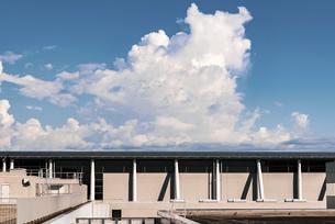 【夏】建物の上に入道雲が流れている風景 フィルム風の写真素材 [FYI04874565]
