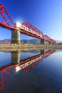 赤い鉄橋を渡る別所線の1000系赤帯と千曲川の水鏡の写真素材 [FYI04875447]