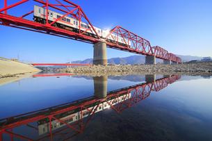 赤い鉄橋を渡る別所線の1000系赤帯と千曲川の水鏡の写真素材 [FYI04875448]