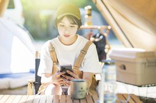キャンプをして、テントの中でスマートフォンを操作する若い女性の写真素材 [FYI04875855]