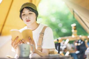ソロキャンプイメージ・本を読む若い女性の写真素材 [FYI04875972]
