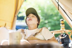 ソロキャンプイメージ・テントの前で昼寝する若い女性の写真素材 [FYI04875978]