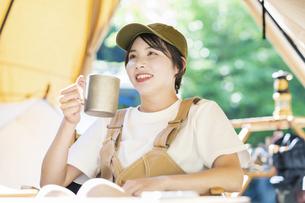ソロキャンプイメージ・お酒を飲む若い女性の写真素材 [FYI04875985]