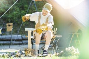 ソロキャンプイメージ・薪を割る若い女性の写真素材 [FYI04875992]