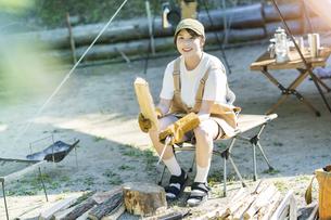 ソロキャンプイメージ・薪を割る若い女性の写真素材 [FYI04875994]