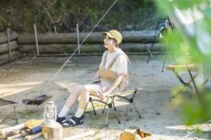 ソロキャンプイメージ・テントを張ってくつろぐ若い女性の写真素材 [FYI04875995]
