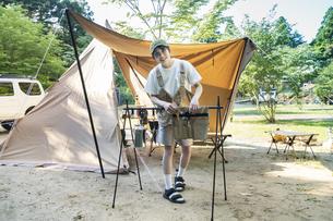 ソロキャンプイメージ・テントを張ってくつろぐ若い女性の写真素材 [FYI04875998]