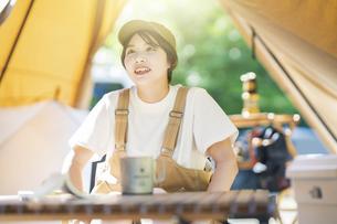 ソロキャンプイメージ・テントを張ってくつろぐ若い女性の写真素材 [FYI04876001]
