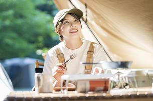 ソロキャンプイメージ・テントを張ってくつろぐ若い女性の写真素材 [FYI04876005]