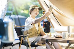 ソロキャンプイメージ・スマートフォンで自撮りする女性 の写真素材 [FYI04876009]