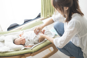赤ちゃんのオムツを替えるお母さんの写真素材 [FYI04876177]