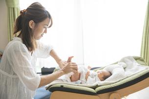 赤ちゃんのオムツを替えるお母さんの写真素材 [FYI04876178]