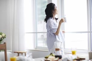コーヒーカップを持ち窓の外を見る女性の写真素材 [FYI04877380]