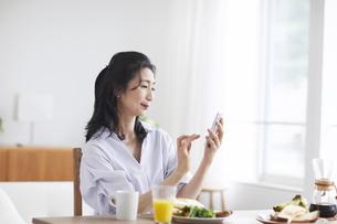 スマホを見ながら食事をする女性の写真素材 [FYI04877383]
