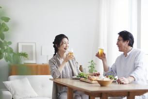 ビールを飲みながら食事をする夫婦の写真素材 [FYI04877384]