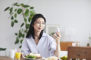 スマホを見ながら食事をする女性の写真素材 [FYI04877386]