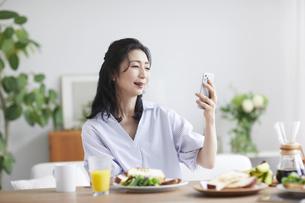 スマホを見ながら食事をする女性の写真素材 [FYI04877389]