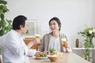 ビールを飲みながら食事をする夫婦の写真素材 [FYI04877422]