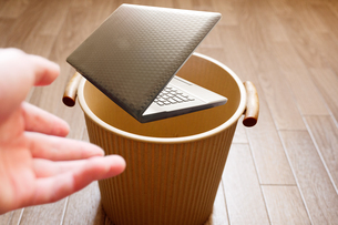 分厚く重い旧式のノートパソコンをゴミ箱に投げ捨てるの写真素材 [FYI04879110]