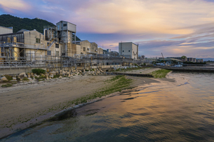 【産業】海沿いの夕方の工場の写真素材 [FYI04879875]