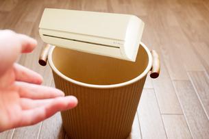 旧式のエアコンをゴミ箱に投げ捨てるの写真素材 [FYI04879916]