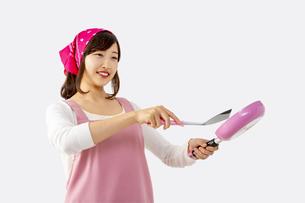 白背景前でフライパンで料理を作る笑顔の若い女性1人の写真素材 [FYI04880452]