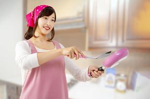 キッチンでフライパンで料理を作る笑顔の若い女性1人の写真素材 [FYI04880458]