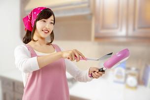 キッチンでフライパンで料理を作る笑顔の若い女性1人の写真素材 [FYI04880459]