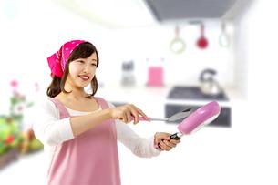 キッチンでフライパンで料理を作る笑顔の若い女性1人の写真素材 [FYI04880460]