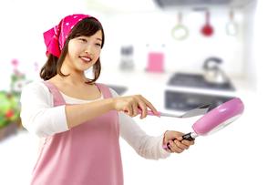 キッチンでフライパンで料理を作る笑顔の若い女性1人の写真素材 [FYI04880461]