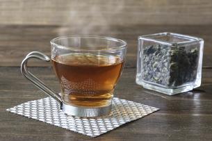 ガラスキューブ容器に入れたウーロン茶葉と一杯のウーロン茶の写真素材 [FYI04880621]