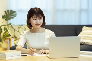 リビングでオンライン学習中の若い女性の写真素材 [FYI04881103]