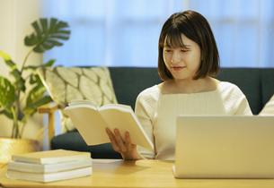 リビングでオンライン学習中の若い女性の写真素材 [FYI04881105]