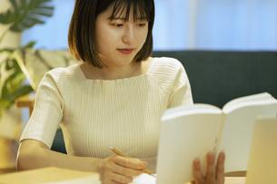 リビングでオンライン学習中の若い女性の写真素材 [FYI04881106]