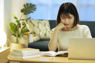 リビングでオンライン学習中の若い女性の写真素材 [FYI04881108]
