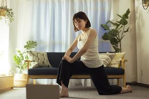 リビングでフィットネスを行う若い女性の写真素材 [FYI04881113]