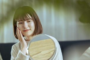 リビングで肌のケアをする若い女性の写真素材 [FYI04881137]