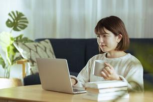 リビングでオンライン学習中の若い女性の写真素材 [FYI04881139]