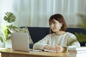 リビングでオンライン学習中の若い女性の写真素材 [FYI04881142]