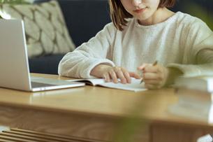 リビングでオンライン学習中の若い女性の写真素材 [FYI04881144]