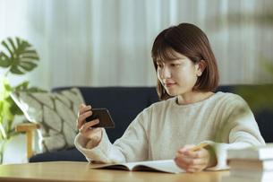 リビングでオンライン学習中の若い女性の写真素材 [FYI04881146]