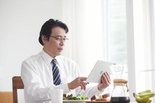 タブレット端末を見ながら朝食をとる男性の写真素材 [FYI04881349]
