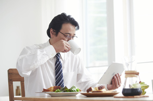 タブレット端末を見ながら朝食をとる男性の写真素材 [FYI04881352]