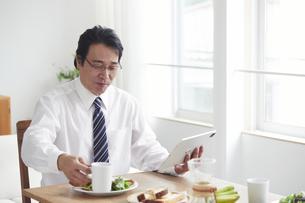 タブレット端末を見ながら朝食をとる男性の写真素材 [FYI04881354]